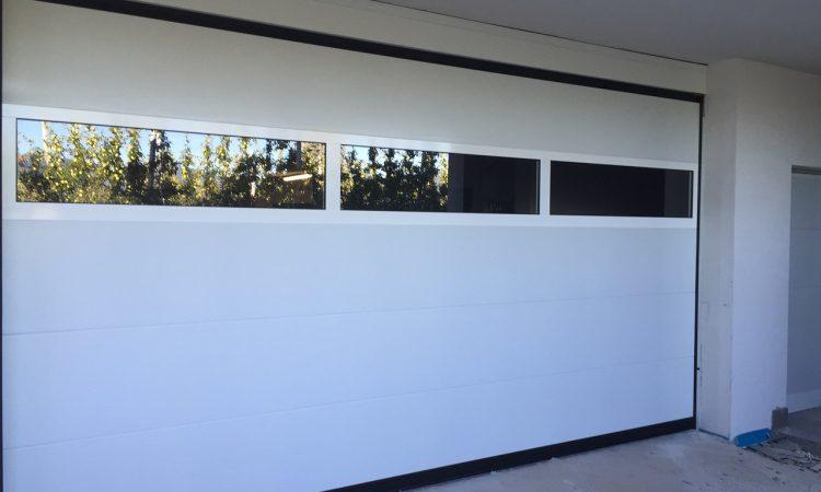 Portone sezionale con sezione in vetro stratificato